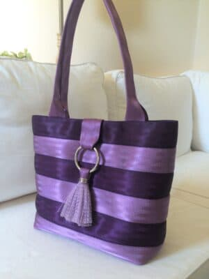 purse in two tones of purple sitting on couch