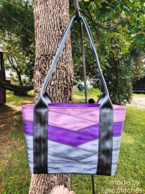 front view of purple and grey motor city seat belt tote on tree
