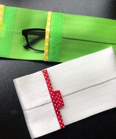 one green and one white glasses cases on black table