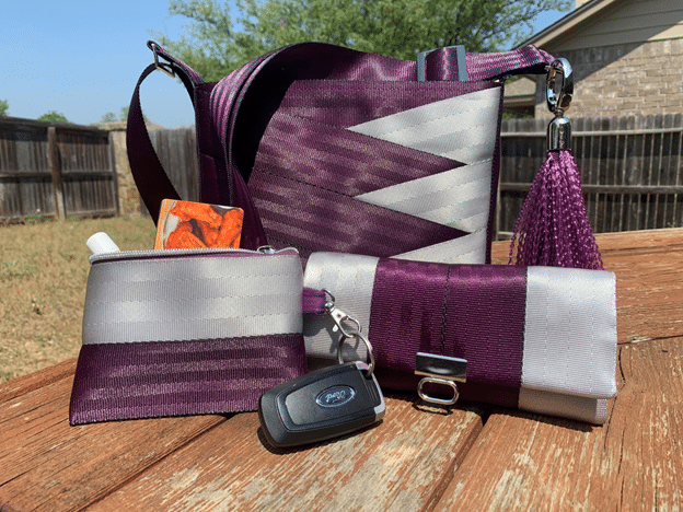 Purse, pouch and wallet made from purple and silver seat belts sit on a wooden table.