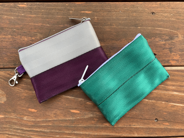 Two zippered seat belt pouches sitting on a wooden surface. One is silver and purple, the other is green