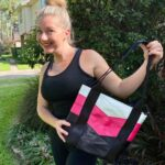 blonde women holding tote bag and smiling