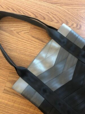 seat belt tote in shades of grey laying on floor