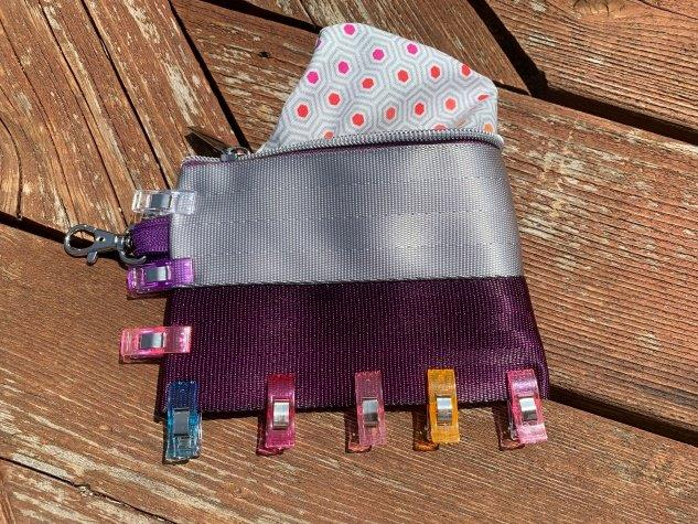 Pouch is turned right side out and and lining is show peeking out. Clips are around bottom and side edge with swivel clip