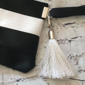 white tassel attached to black and white pouch