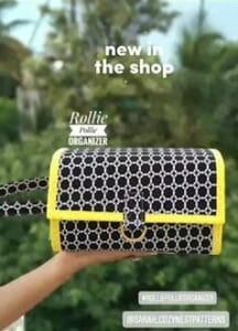 hand holding a navy and yellow rollie pollie organizer