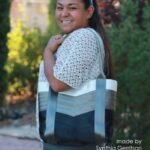 woman holding white grey and black seat belt tote